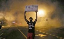 Ferguson rebel holds up sign