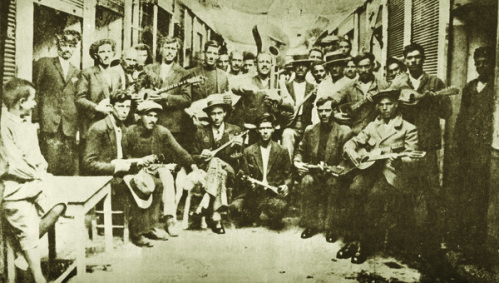 Giorgos Batis (in the middle with guitar) with a group of musicians. Markos Vamavakaris is standing fourth from the left. Piraeus, 1933